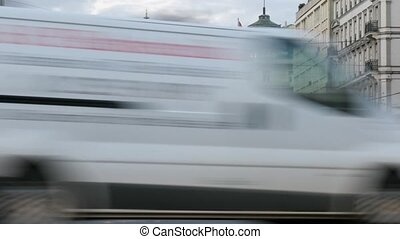 Cars go across evening Vienna towards building of State...