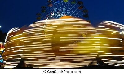 Fellow merry-go-round is shone by multi-colored light in park Sokolniki