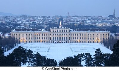 Schoenbrunn palace stands against evening city, time lapse