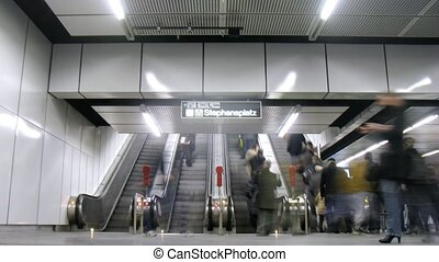Passengers go on escalator to subway at station...