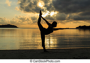 Silhouette of a beautiful yoga girl at sunrise on the beach