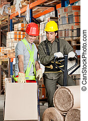 Foreman Showing Something To Coworker At Warehouse - Foreman...