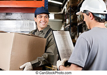 Warehouse Worker Looking At Supervisor With Clipboard -...