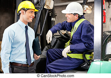 Forklift Driver Communicating With Supervisor - Young...