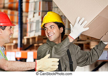 Foreman With Coworker Lifting Cardboard Box At Warehouse -...