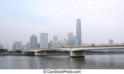 Cars go on bridge standing in front of Zhujiang New Town in afternoon