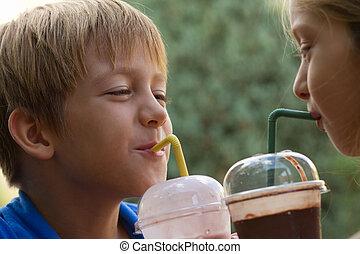 Funny little children drink milkshake