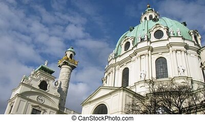Towers of Karlskirche Church stand against floating clouds,...