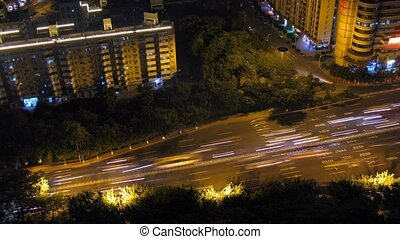 Cars quickly go on road surrounded with trees at night, time...