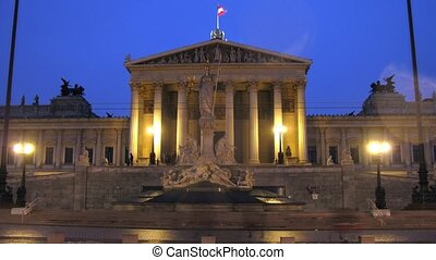 Tourists walk near Austrian parliament in evening - VIENNA -...