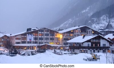 Hotel stands near road in valley where cars go and ly snow,...