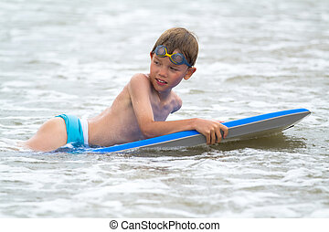 Young child with a bodyboard on the beach - Young boy with a...