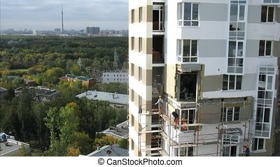 Workers mount scaffold at height on wall of house, time...