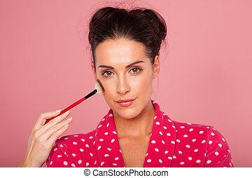 Glamorous woman applying blusher