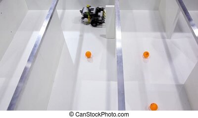 Robot moves in labyrinth and collects orange balls, view...
