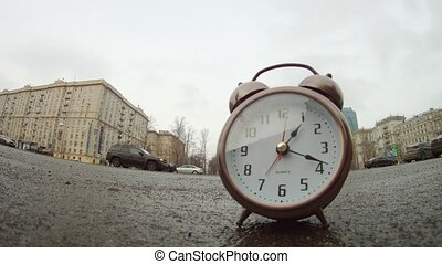Clocks stands on roadside of road in front of moving cars -...