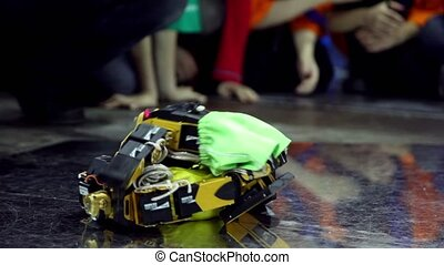 Two toy robots in shorts lay on each other, falls and stand...