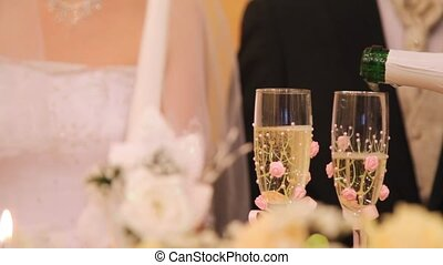 In two glasses champagne on wedding is poured - In two...