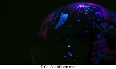 Transparent sphere with world map on it spins in color light...