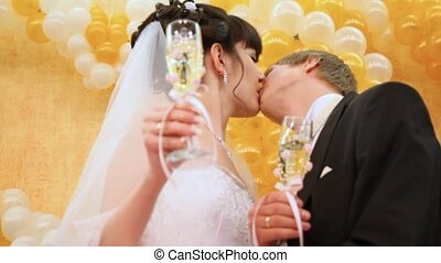 Newly-married couple kisses champagne glasses in hands against wall