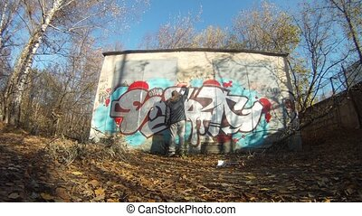 Teenager draw graffiti on wall in autumn on Losinyj island -...