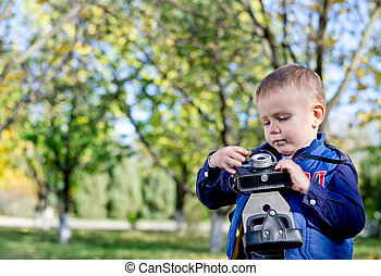Little boy playing with a vintage camera