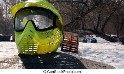 Yellow helm for paintball lay at background of playground -...