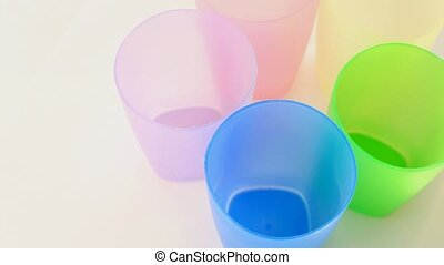 Five multi-colored glass glasses rotates on white background
