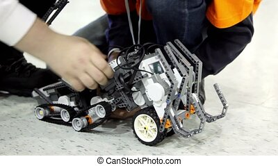 People operate with toy robot on floor, only legs and hands...
