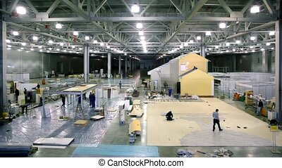 Labourers work on building site in exhibition hangar -...