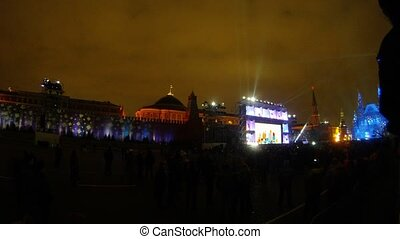 Many people stand and look laser show on Red Square festival CIRCLE OF LIGHT