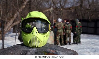 Paintball teams talk together, helm lay at foreground -...