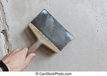 trowel in a hand in front of plastered wall
