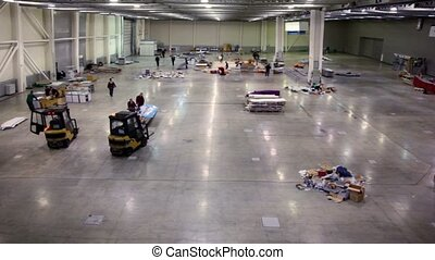 Two loaders stand in empty hangar with several trash piles, people walk around