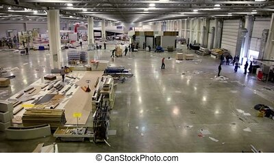 Many people work in large hangar with building materials