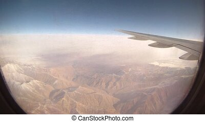 Mountains are visible from window of flying plane, time...