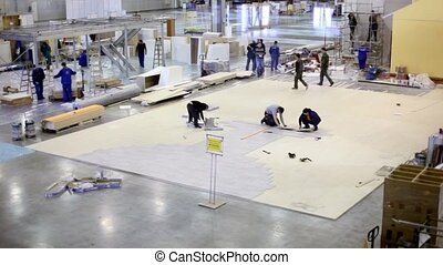 Several workers make floor and other build house in exhibition hangar