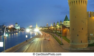 Cars and people go on Kremlin embankment  in evening