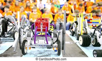 Toy robots stand on table at background of many children in...