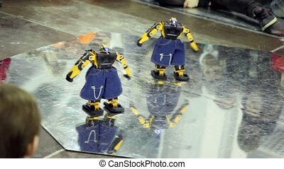 Two toy robots in jeans shorts dance on plate - Two toy...