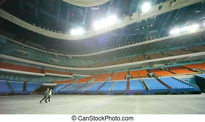 policeman and worker of protection go on huge empty hall of...