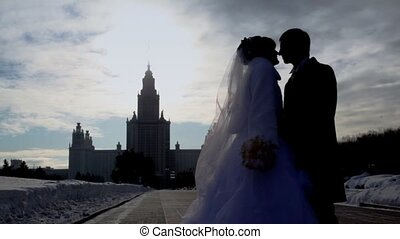 Newly-married couple stands on avenue in winter