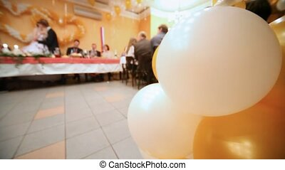 Close up balloons, behind newly-married couple kiss standing...
