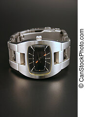 Wristwatch - A silver metallic watch islolated on a black...
