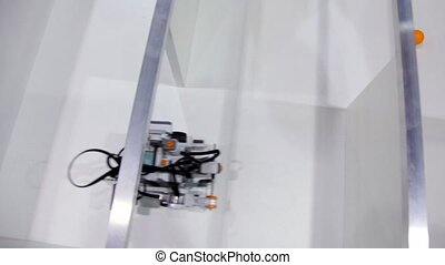 Robot moves in maze and collects orange balls, view from...
