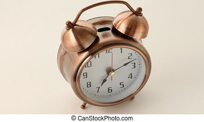 old fashioned round alarm clock from copper rotates on white...
