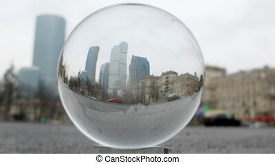 Business center Moscow City is visible through transparent glass ball lying on road