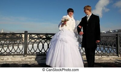 Newly-married couple is turned together on bridge in winter