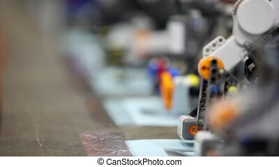 Robots stand on table, closeup view with focus changes