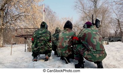 Four men paintball team start run to take position at begin...